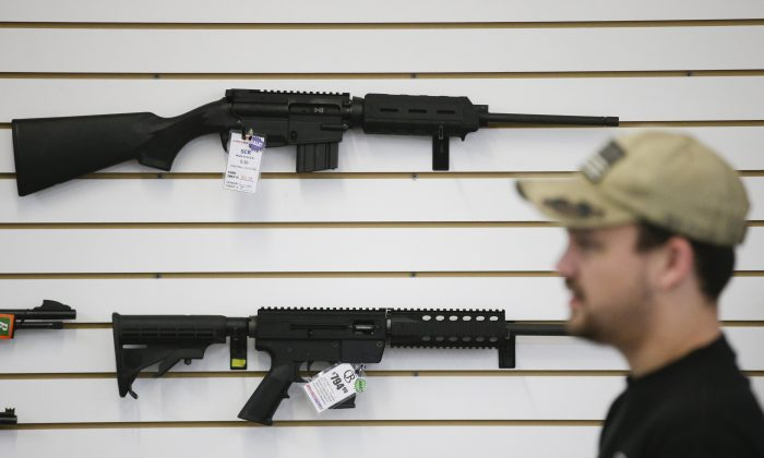 In this Dec. 9, 2015, photo, a sales associate walks past semiautomatic rifles at Bullseye Sport gun shop in Riverside, Calif. The massacre at Sandy Hook elementary school in which a mentally disturbed young man killed 26 children and teachers galvanized calls across the nation for tighter gun controls. But in the three years since, many states have moved in the opposite direction, embracing the National Rifle Associations response that more good guys with guns are whats needed to limit the carnage of mass shootings. (AP Photo/Jae C. Hong)