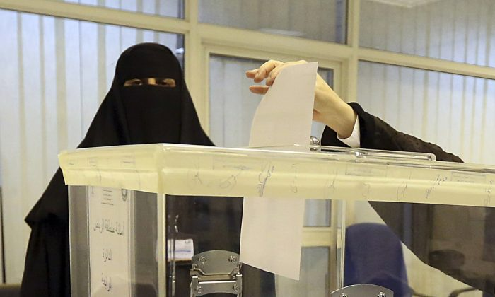 Saudi women vote at a polling center during the municipal elections, in Riyadh, Saudi Arabia, Saturday, Dec. 12, 2015. Women across Saudi Arabia marked a historic milestone on Saturday, both voting and running as candidates in government elections for the first time, but just outside polling stations they waited for male drivers—a reminder of the limitations still firmly in place. (AP Photo/Aya Batrawy)