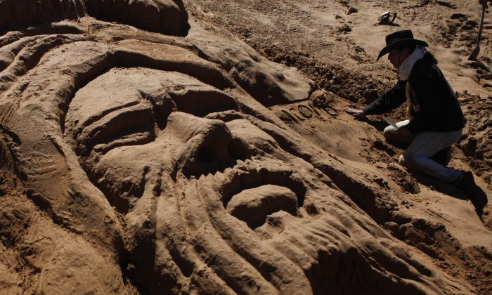 A man works on a sand sculpture depicting Jesus Christ during Holy Week in Arenal de Cochiraya, Oruro, Bolivia, Friday, April 22, 2011. (AP Photo/Juan Karita)
