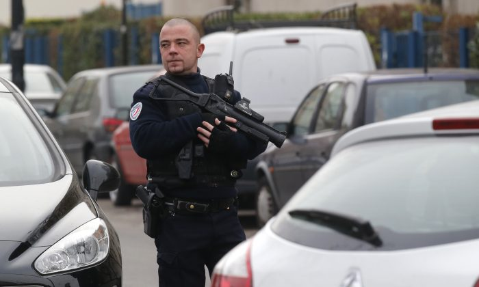 A police officer patrols near a pre-school, after a masked assailant with a box-cutter and scissors who mentioned the Islamic State group attacked a teacher, Monday, Dec.14, 2015 in Paris suburb Aubervilliers.  (AP Photo/Michel Euler)