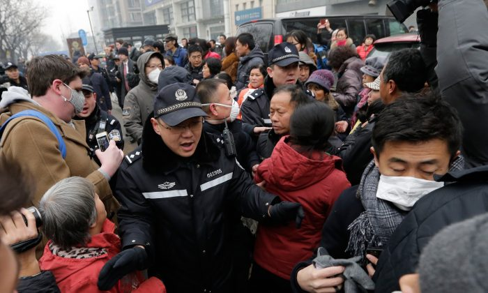 Police officers push away supporters of rights lawyer Pu Zhiqiang and foreign journalists near the Beijing Second Intermediate People's Court in Beijing, Monday, Dec. 14, 2015. (AP Photo/Andy Wong)