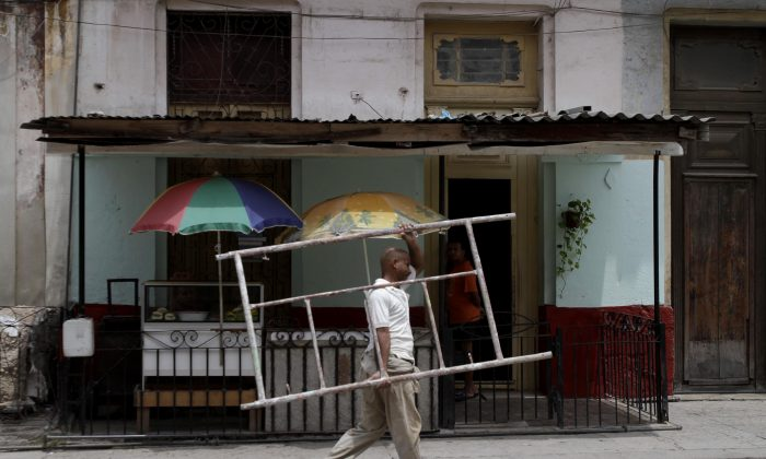 Ruben Font carries a scaffold piece to his home in Havana, Cuba, on May 23, 2011. Cuba has reached a landmark agreement with foreign creditors over billions of dollars in unpaid debt dating back 25 years. (AP Photo/Franklin Reyes)