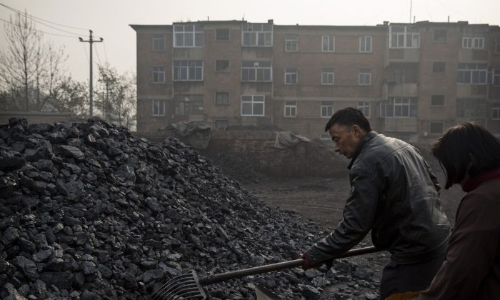 Chinese laborers work at a coal depot, which manufactures coal used for cooking and heating in Hebei, outside Beijing, China, on Nov. 21, 2014. (Kevin Frayer/Getty Images)
