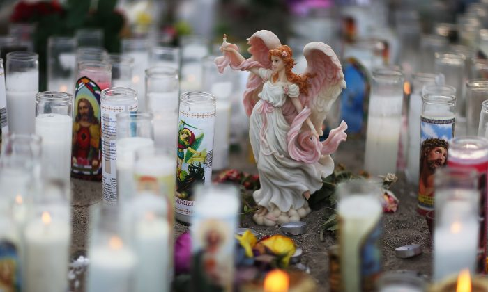 An angel statue is seen among candles at a makeshift memorial near the Inland Regional Center in San Bernardino, Calif., on Dec. 6, 2015. (Joe Raedle/Getty Images)