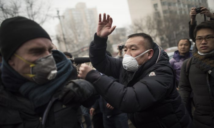 Chinese police push away journalists and supporters of human rights lawyer Pu Zhiqiang demonstrating near the Beijing Second Intermediate People's Court in Beijing on Dec. 14, 2015. (FRED DUFOUR/AFP/Getty Images)