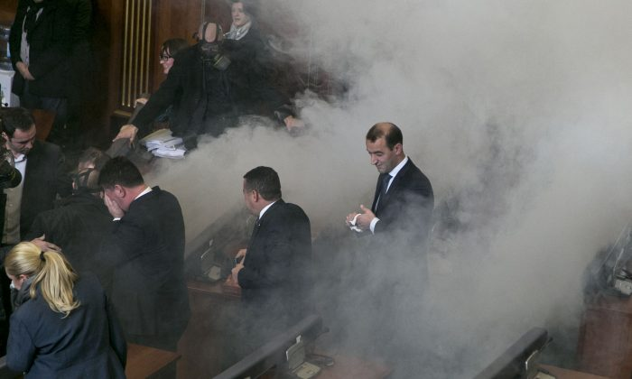 Lawmakers react as opposition lawmakers release tear gas canisters disrupting a parliamentary session in Kosovo capital Pristina on Monday Dec. 14, 2015. (AP Photo/Visar Kryeziu)
