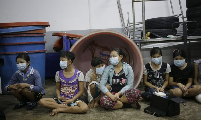 In this Monday, Nov. 9, 2015 photo, children and teenagers sit together to be registered by officials during a raid on a shrimp shed in Samut Sakhon, Thailand. (AP Photo/Dita Alangkara)