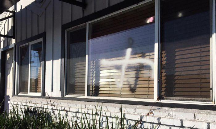 This photo provided by the Ahmadiyya Muslim Community muslimsforpeace.org shows crosses in spray paint vandalizing windows at the Ahmadiyya Muslim Community Baitus-Salaam Mosque in Hawthorne, Calif., Sunday, Dec. 13, 2015. (Ahmadiyya Muslim Community muslimsforpeace.org via AP)