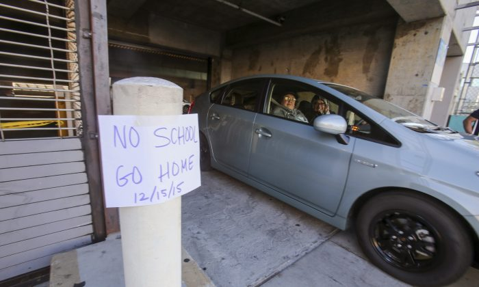 """A vehicle leaves the Miguel Contreras Learning Complex past a sign """"No School Go Home"""" is displayed Tuesday, Dec. 15, 2015, in Los Angeles.  All schools in the vast Los Angeles Unified School District, the nation's second largest, have been ordered closed due to an electronic threat Tuesday.(AP Photo/Ringo H.W. Chiu)"""