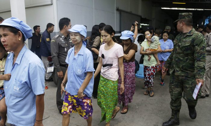 In this Monday, Nov. 9, 2015 photo, Burmese workers are escorted by soldiers and police officers as they leave a shrimp shed after a raid conducted by Thailand's Department of Special Investigation in Samut Sakhon, Thailand. (AP Photo/Dita Alangkara)