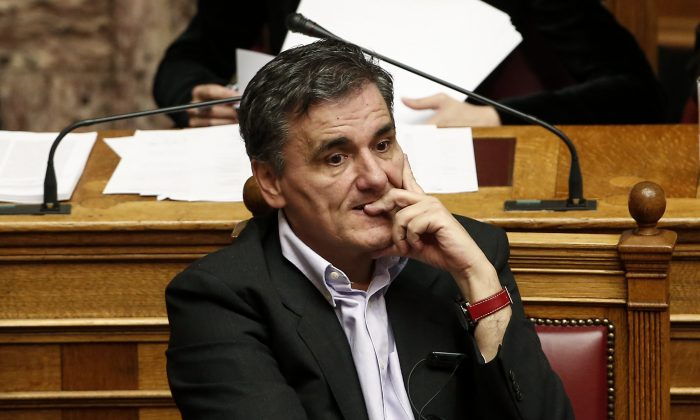 Greece's Finance Minister Euclid Tsakalotos attends a parliamentary session ahead of a vote, in Athens, on Tuesday, Dec. 15, 2015. Lawmakers in Greece are set to sanction the right to sell bad business loans from local banks to overseas funds as part of a new austerity bill demanded by bailout lenders from the rest of the eurozone. (AP Photo/Yorgos Karahalis)
