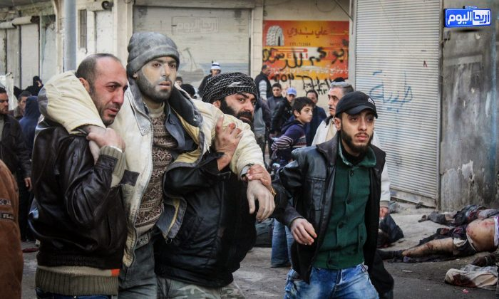 In this photo provided by the Syrian anti-government activist group Ariha Today, which has been authenticated based on its contents and other AP reporting, Syrian citizens help an injured man after airstrikes believed to be carried out by Russian warplanes in the center of Ariha town in the northwestern province of Idlib, Syria, Sunday, Nov. 29, 2015. (Ariha Today via AP)