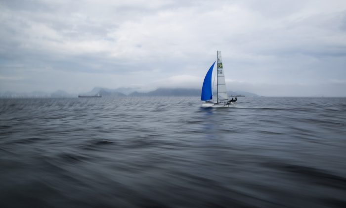 Brazilian athletes Samuel Albrecht and Isabel Swan practice in Guanabara Bay in Rio de Janeiro, Brazil, on Nov. 3, 2015. Since August, The Associated Press has expanded its testing to include offshore sampling sites inside sailing circuits in the bay and in the middle of the Rodrigo de Freitas Lagoon where rowing and canoeing lanes were located during recent test events. (AP Photo/Felipe Dana)