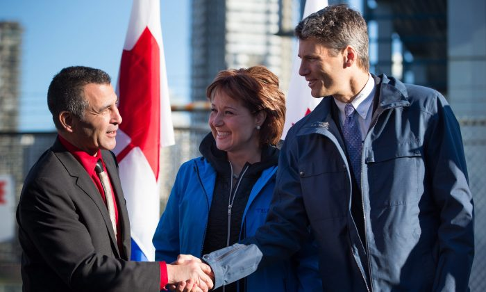 Fisheries, Oceans and the Canadian Coast Guard Minister Hunter Tootoo (L) shakes hands with Vancouver Mayor Gregor Robertson as B.C. Premier Christy Clark looks on after Tootoo announced the federal government's commitment to reopening the Kitsilano Coast Guard facility, in Vancouver, Dec. 16. (THE CANADIAN PRESS/Darryl Dyck)