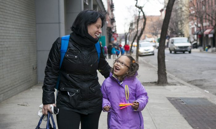 Jenny Pena walks her daughter to school at the Success Academy Hell's Kitchen in New York on March 17. (Samira Bouaou/Epoch Times)