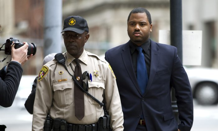 Officer William Porter, right, one of six Baltimore city police officers charged in connection to the death of Freddie Gray, arrives at a courthouse as jury deliberations continue in his trial, Wednesday, Dec. 16, 2015, in Baltimore Md. (AP Photo/Jose Luis Magana)