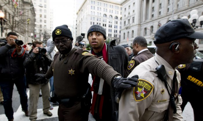 A demonstrator is arrested outside of the courthouse after a mistrial of Officer William Porter, one of six Baltimore city police officers charged in connection to the death of Freddie Gray, on Wednesday, Dec. 16, 2015, in Baltimore. (AP Photo/Jose Luis Magana)