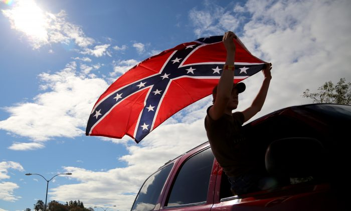 A man waves a Confederate battle flag as he drives away from Roseburg Regional Airport in Roseburg, Ore. in a file photograph. (Ryan Kang/AP Photo)