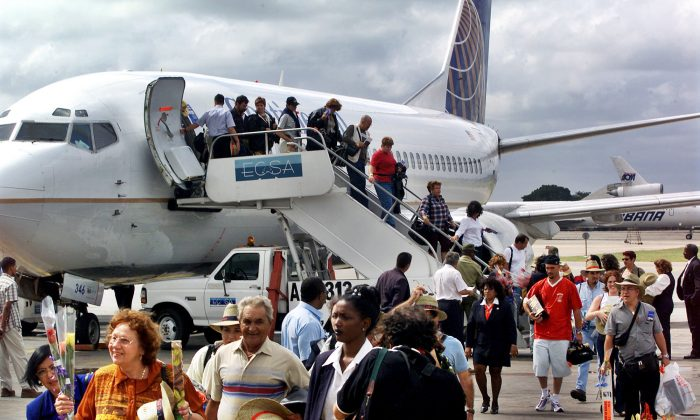 The first passengers of the first flight of Continental Airlines from Miami Florida, arrives at the Jose Marti Airport of Havana, Cuba, on Nov. 1, 2001. The United States and Cuba have reached an understanding on restoring regularly scheduled commercial flights, Cuban and American officials said Wednesday, Dec. 16, 2016 on the eve of the anniversary of detente between the Cold War foes. (AP Photo/Jose Goitia)