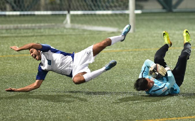 Lucky Mile player Shaun Melwani takes a tumble as Citizen goalkeeper saves the ball during Citizen's 4-1 win in HKFA first division game at Hong Kong Football Club on Sunday Dec 13, 2015. (Bill Cox/Epoch Times)