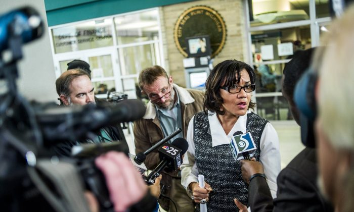 A swarm of reporters surround Flint Mayor Karen Weaver to ask question after a news conference on Tuesday Dec. 15, 2015, at City Hall in Flint, Mich. Flint's mayor declared a state of emergency due to problems with the city's water system caused by using water from the Flint River, saying the city needs more federal help. (Jake May /The Flint Journal-MLive.com via AP) LOCAL TELEVISION OUT; LOCAL INTERNET OUT; MANDATORY CREDIT