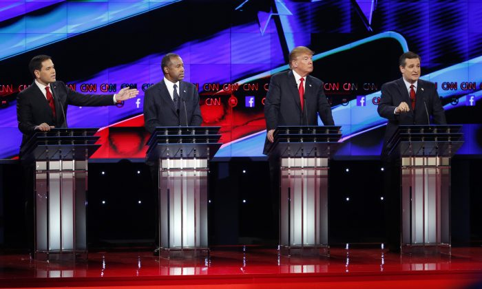 Marco Rubio, left, and Ted Cruz, right, both speak as Ben Carson, second from left, and Donald Trump, second from right, look on during the CNN Republican presidential debate at the Venetian Hotel & Casino on Tuesday, Dec. 15, 2015, in Las Vegas. (AP Photo/John Locher)