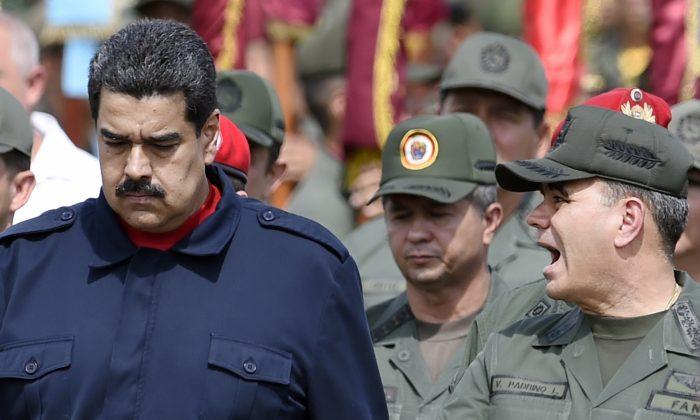 Venezuelan President Nicolás Maduro (L) walks with Venezuelan Defense Minister Padrino López (R) during a military parade in Caracas on Dec. 12, 2015. (Juan Barreto/AFP/Getty Images)
