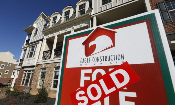FILE - In this Jan. 8, 2015, file photo, a sign with a sold sticker is posted in front of a row of new town homes in Richmond, Va. (AP Photo/Steve Helber, File)
