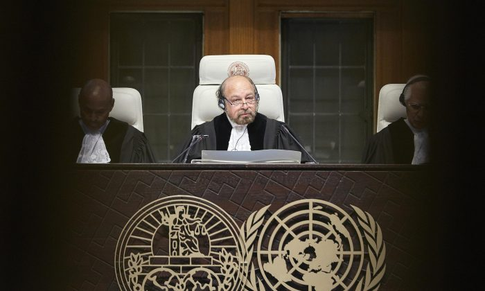 Presiding Judge Ronny Abraham of France, during the reading of the Judgement of the World Court session in The Hague, Netherlands, Wednesday, Dec. 16, 2015. The court delivered its judgment in the case between Nicaragua and Costa Rica who are trying to settle a double dispute over the San Juan river, which makes up the border between the two countries. (AP Photo/Phil Nijhuis)