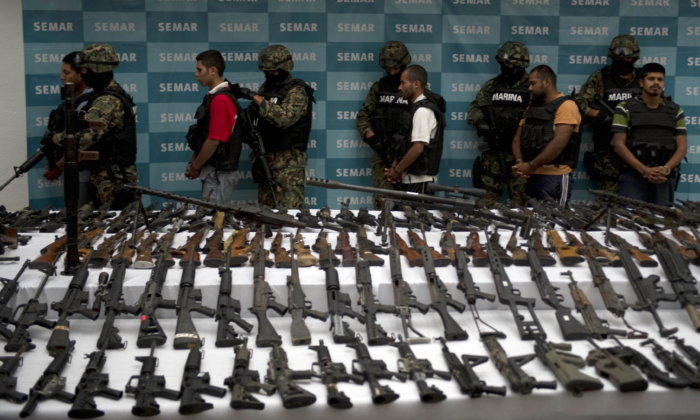 Mexican marines escort five alleged drug traffickers of the Zetas drug cartel in front seized grenades, firearms, cocaine, and military uniforms in Mexico City on June 9, 2011. (Yuri Cortez/AFP/Getty Images)