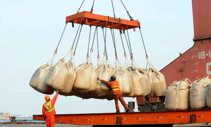 Workers unload goods from a ship at the port in Lianyungang, east China's Jiangsu province on February 12, 2014. (STR/AFP/Getty Images)
