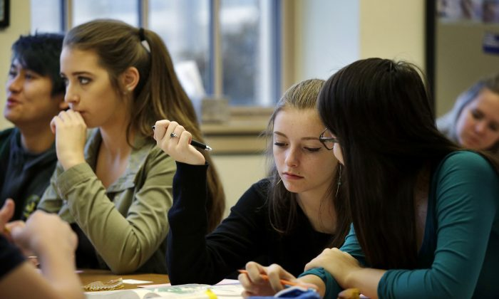 In this photo taken Nov. 23, 2015, sophomores Kendra Mitchell, second left, and Katie Benmar, sit with other first-period students in a geography class at Roosevelt High School in Seattle. (AP Photo/Elaine Thompson)