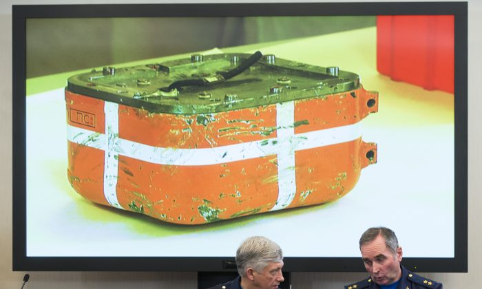 Russian aerospace forces Lt.-Gen. Sergei Dronov, left, and Lt.-Gen. Sergei Bainetov talk, as an image of a flight data recorder from the Russian warplane downed by Turkey is displayed on a screen in the background. during a news conference, in Moscow, Russia, Friday, Dec. 18, 2015. (AP Photo/Alexander Zemlianichenko)