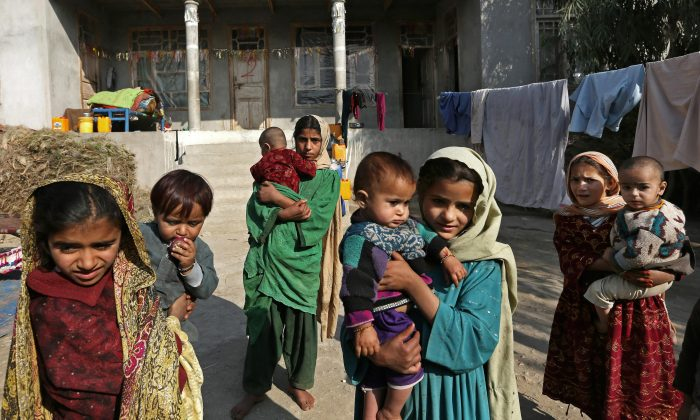 Internally displaced girls hold babies after their family left their village in Behsood district of Jalalabad east of Kabul, Afghanistan, on Nov. 30, 2015. It is a makeshift camp with thousands of people who left their homes to escape what is turning out to be an increasingly vicious war for control of the region between the Taliban and fighters of Afghanistan's Islamic State affiliate. (AP Photo/Rahmat Gul)