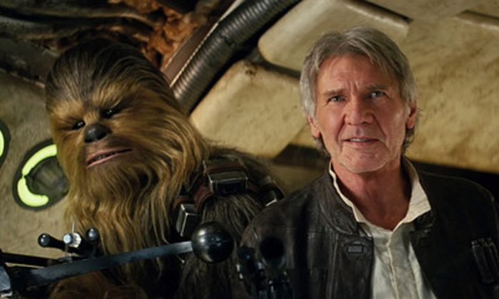 """This photo provided by Lucasfilm shows Peter Mayhew as Chewbacca and Harrison Ford as Han Solo in """"Star Wars: The Force Awakens,"""" directed by J.J. Abrams. Lawrence Kasdan co-wrote the screenplay with Abrams. The movie opens in U.S. theaters on Friday, Dec. 18, 2015. (Film Frame/Lucasfilm via AP) -"""