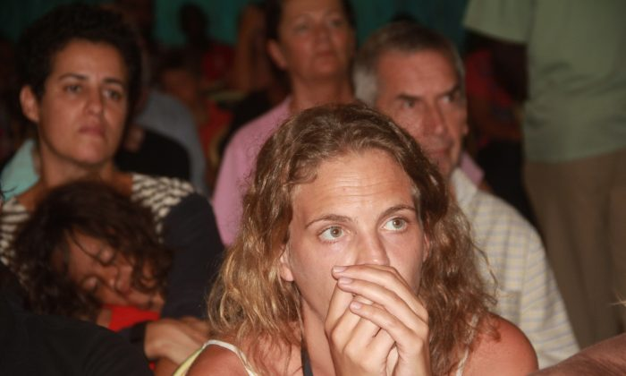 Passengers who were onboard the AirFrance plane forced to land in Mombasa, Kenya, Sunday Dec. 20, 2015, react after they were officially informed of the bomb-scare in the plane they were traveling in.  The passengers are due to be evacuated from Mombassa later Sunday.  Six passengers are being questioned over the incident,  a Kenyan police official said Sunday, also advising that no explosives have been found on the suspicious device.(AP Photo)