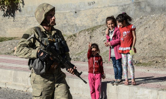 A Kurdish child flashes the victory sign at a Turkish soldier following clashes between Turkish forces and Kurdish militans in Silvan on Nov. 14, 2015. Turkish security forces backed up by tanks and combat helicopters launched a large-scale operation against the militants in the battered town of Silvan, which has been under a punishing curfew for nine days. (Ilyas Akengin/AFP/Getty Images)