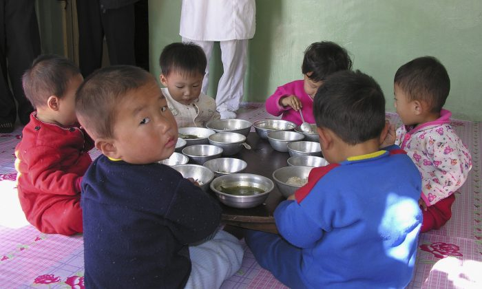 """Children attend a government run nursery with special food provided by the World Food Program in Pyongyang, North Korea, on Oct. 18, 2005. According to the WFP website, """"Child malnutrition for children under the age of seven [in N. Korea] has improved over the years but is still high. In the latest survey, carried out in 2002, 40% of the children were stunted, 20% were underweight and 8% were wasted. The stunting rate is regarded as a severe public health problem (WHO standards)."""" (Gerald Bourke/WFP via Getty Images)"""