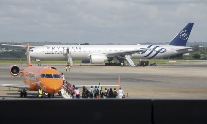 An Air France plane which made an emergency landing is seen behind passengers boarding on a small jetliner at Moi International Airport in Mombasa, Kenya, on Dec. 20, 2015. The Boeing 777 Air France flight 463 from Mauritius to Paris was forced to land in the Kenyan coastal city of Mombasa after a device suspected to be a bomb was found in the lavatory, a Kenyan police official said Sunday. The passengers shown in this photo are not the Air France plane evacuees. (AP Photo/Edwin Kana)