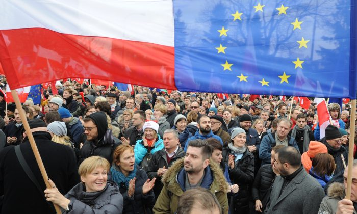Protesters wave Polish and European Union flags during an anti government demonstration in Warsaw, Poland, on Dec. 19, 2015. Thousands of Poles participated in demonstrations across Poland to protest moves by the new right-wing government to neutralize the Constitutional Tribunal as a check on its power. (AP Photo/Alik Keplicz)