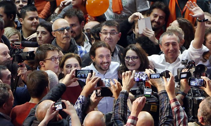 Pablo Iglesias (C), leader of Podemos party, arrives for a closing campaign rally in Valencia, Spain, on Dec. 18, 2015. The rise of two influential new parties to challenge the two traditional parties of government has injected tension and suspense into Sunday's ballot, where voters will give their verdict on promises to end high unemployment and corruption scandals in the European Union's fifth-largest economy. (AP Photo/Alberto Saiz)