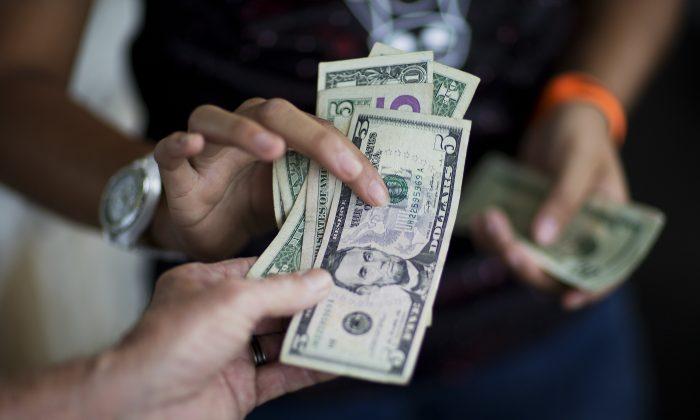 A customer, bottom, pays for goods while shopping at the Atlanta Farmers Market in Atlanta, on June 6, 2015. (David Goldman, File/AP Photo)