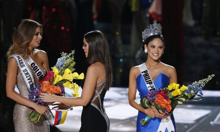 Former Miss Universe Paulina Vega (C) takes away the flowers and sash from Miss Colombia Ariadna Gutierrez (L) before giving it to Miss Philippines Pia Alonzo Wurtzbach (R) at the Miss Universe pageant in Las Vegas on Dec. 20. (AP Photo/John Locher)