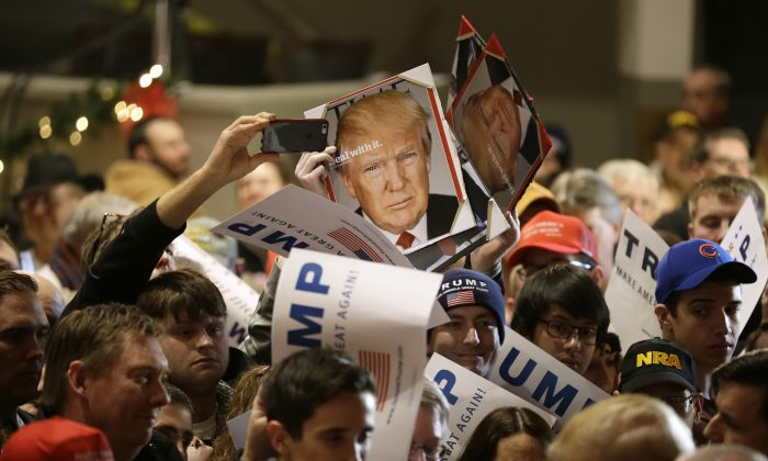 Audience members hold signs to be autographed by Republican presidential candidate Donald Trump during a campaign rally at the Veterans Memorial Building, Saturday, Dec. 19, 2015, in Cedar Rapids, Iowa. (AP Photo/Charlie Neibergall)
