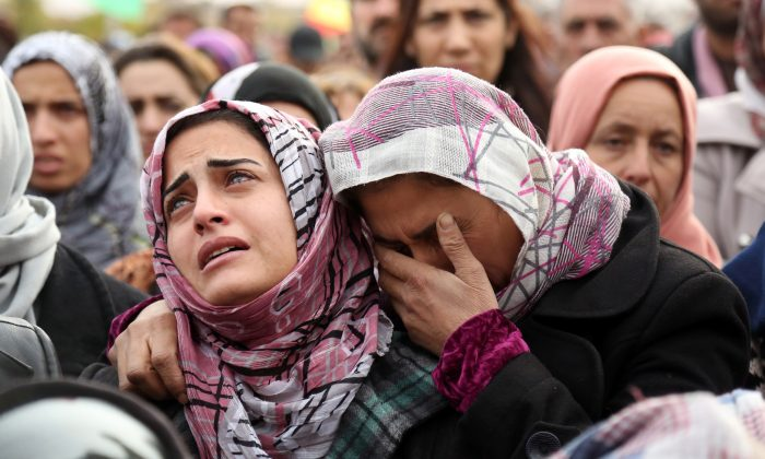 The sister (L) of Mohammed Ismael, who died in one of three recent suicide car bombings claimed by the Islamic State in the town of Tal Tamr, mourns during his funeral in Qamishli City, Hasakeh Province, Syria, on Dec. 13, 2015. (Delil Souleiman/AFP/Getty Images)