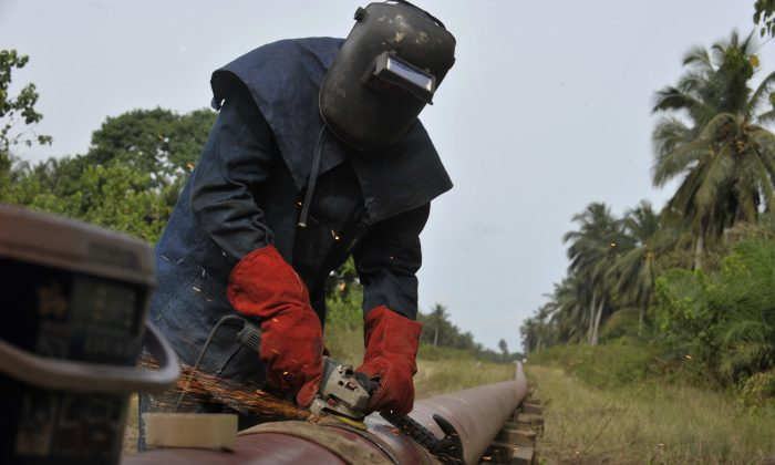 A worker welds an oil pipeline in Jacqueville Town, Ivory Coast, on May 6, 2010. (Issouf Sanogo/AFP/Getty Images)