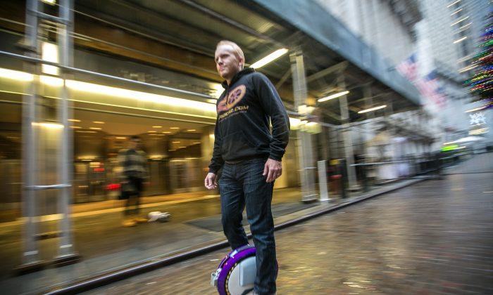 Tim Haden, founder of Hoodriderz, rides a Ninebot One electric wheel next to the New York Stock Exchange building in Manhattan on Dec. 18, 2015. (Benjamin Chasteen/Epoch Times)