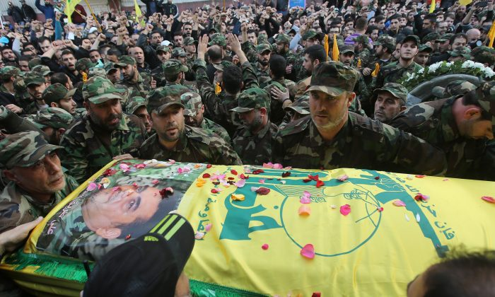 Fighters gather around the coffin of Hezbollah high-profile militant Samir Kantar during his funeral procession, in the southern suburb of Beirut, Lebanon, on Dec. 21, 2015. (AP Photo/Hussein Malla)