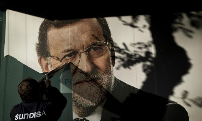 A worker removes a campaign poster for the national elections depicting Spain's acting Prime Minister and Popular Party candidate Mariano Rajoy, in Madrid, Monday, Dec. 21, 2015. Spanish political parties Monday faced what are likely to be tough negotiations to form a government after the country rejected the dominating two-party scene of recent decades and elected a fragmented Parliament. The ruling conservative Popular party came first with 123 seats in Sunday's election but fell far short of a 176 majority needed to govern alone and way below the 186 seats it won in 2011. (AP Photo/Emilio Morenatti)