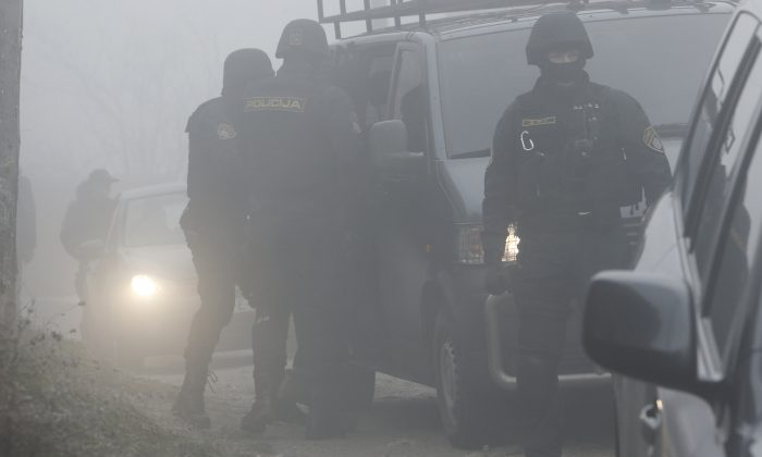 Bosnian policemen secure an urban area in a Sarajevo suburb during a raid targeting suspected terrorists in  Sarajevo, Bosnia, on Tuesday, Dec. 22, 2015. Police in Bosnia detained  11 people Tuesday with suspected of links with the Islamic State group and its militants fighting in Syria and Iraq, the operation, launched on the orders of the state prosecutor's office, was continuing in 13 locations in the wider area of Sarajevo.(AP Photo/Amel Emric)